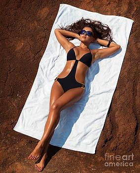Young sexy woman in swimsuit sunbathing by Oleksiy Maksymenko