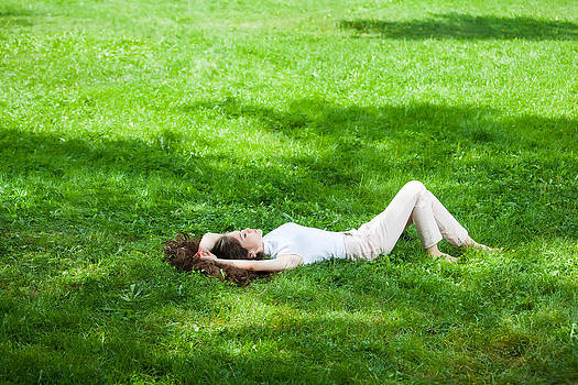 Young Woman Laying On Grass by Cristian Mihaila