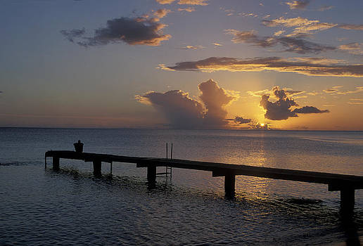 A Lone Figure On The Dock At Sunset, Dominica by James Gritz