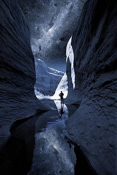 A man hiking in a Lake Powel slot canyon at night with Milky Way by Bryan Allen