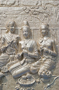 ancient statue on temple wall Thailand  by Wasan Gredpree