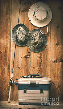 Sandra Cunningham - Hats hanging on wall with fishing equipment