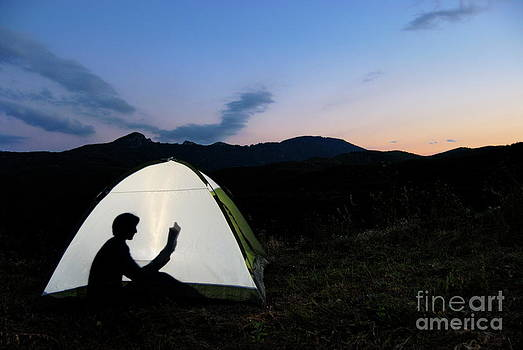 Sami Sarkis - Silhouette of woman reading book in illuminated tent