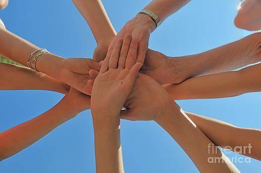 Sami Sarkis - Six people stacking their hands