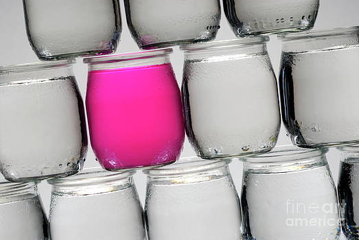 Sami Sarkis - Stack of jars with water one containing pink liquid