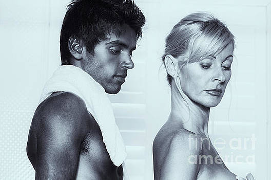 Older Caucasian blonde woman embracing younger man by Amyn Nasser