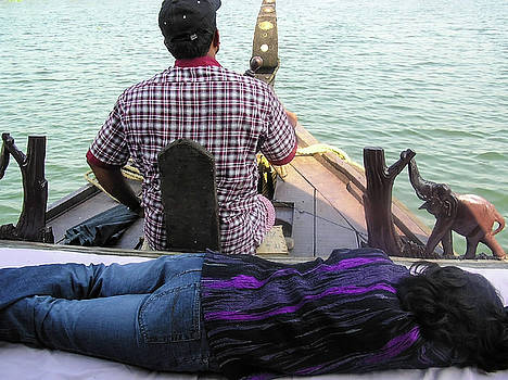 Lady sleeping while boatman steers by Ashish Agarwal