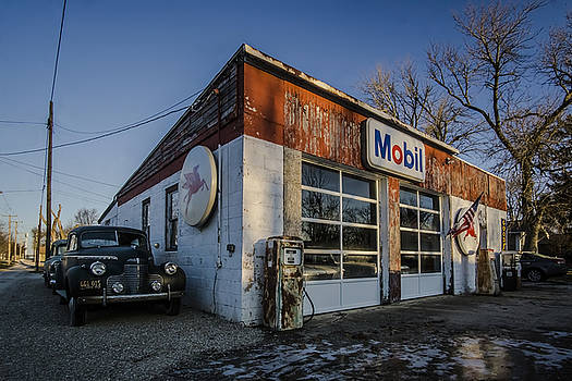 A vintage gas station and vintage cars in early morning light by Sven Brogren