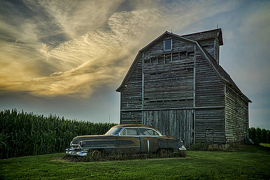 An Old Cadillac by a barn and cornfield by Sven Brogren