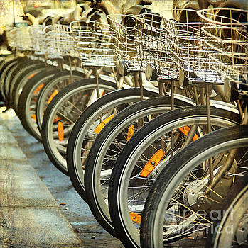 Bicycle in a row in the street by Isabel Poulin