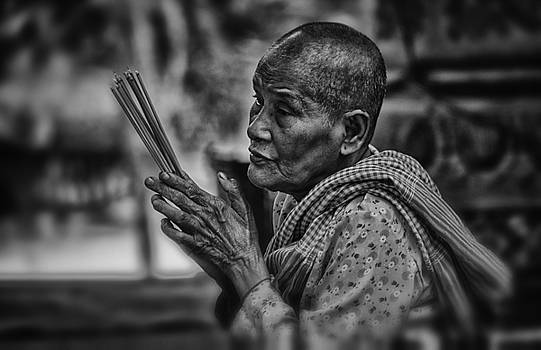 Buddhist nun prays by David Longstreath
