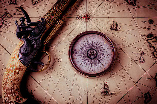 Compass And Pistole On Old Map by Garry Gay