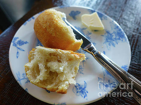 Crusty white roll with knife and butter on blue and white plate by Louise Heusinkveld