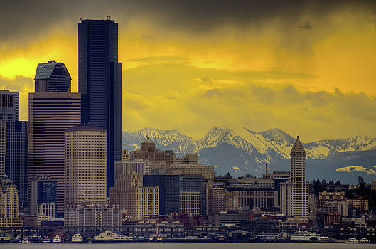 Downtown Seattle with dramatic sky and Cascade Mountains in the  by Jay Mudaliar