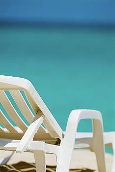 Sami Sarkis - Empty white deck chair on a beach