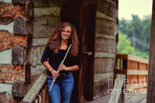Female flute player at log cabin by Dan Friend