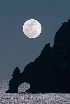 Full moon rising over coastal cliff by David Nunuk