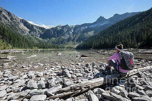 Hiker Relaxes at Avalanche Lake in Glacier National Park by Brandon Alms