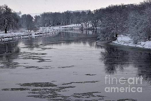Icy river reflections by Laurie Wilcox