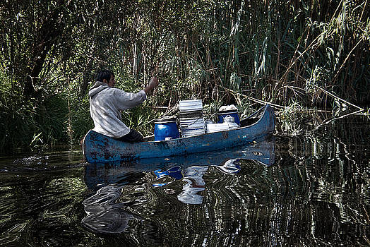Man and Canoe in Xochimilco by David Resnikoff