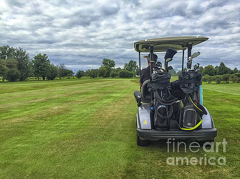 Patricia Hofmeester - Man in golf buggy on course