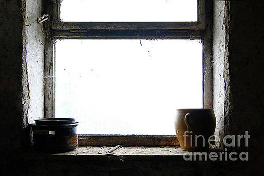 Old pots and stoneware jar on window by Michal Boubin