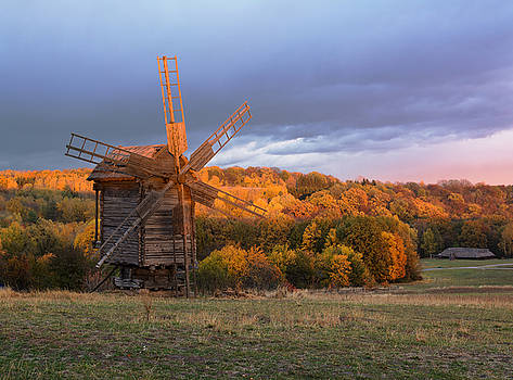 Old wooden windmill in autumn evening. Ukraine, Pyrohiv Museum.  by Sergey Ryzhkov