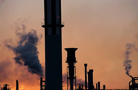 Sami Sarkis - Smoking chimneys of a petroleum refinery at sunset