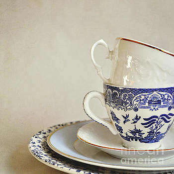 Stacked blue and white china cups and saucers. by Lyn Randle