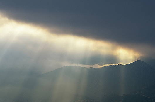 Sami Sarkis - Sunbeams through clouds on mountain range by stormy day