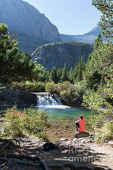 Young Woman Views a Waterfall in Glacier National Park by Brandon Alms