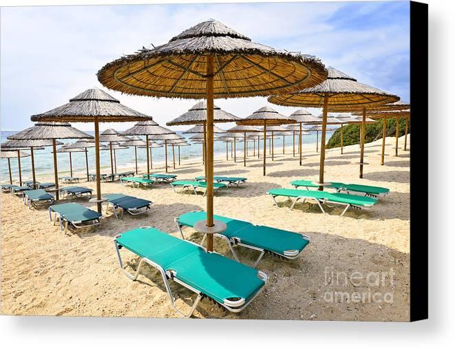 Beach Canvas Print featuring the photograph Beach Umbrellas On Sandy Seashore by Elena Elisseeva