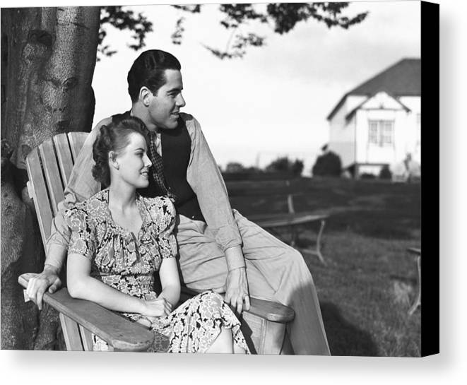 30-34 Years Canvas Print featuring the photograph Couple Relaxing On Deckchair In Garden, (b&w) by George Marks