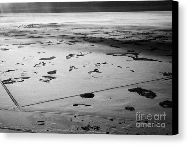 Aerial Canvas Print featuring the photograph aerial view of snow covered prairies and remote isolated farmland in Saskatchewan Canada by Joe Fox