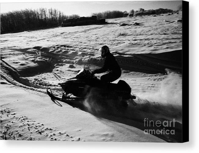 Man Canvas Print featuring the photograph man on snowmobile crossing frozen fields in rural Forget Saskatchewan by Joe Fox