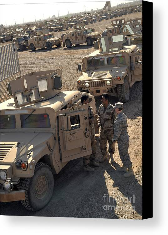 M1114 Canvas Print featuring the photograph U.s. Army Soldier Speaks With Iraqi by Stocktrek Images