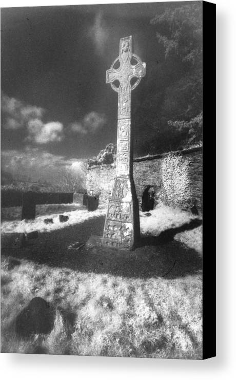 Monument; Stone; Carving; Carved; Shadows; Shadow; Irish; Landscape; Churchyard; Graveyard; Tombstones; Gravestones; Graves; Celtic; Eerie; Atmospheric; Misty; Mist; Solitary Canvas Print featuring the photograph High Cross by Simon Marsden