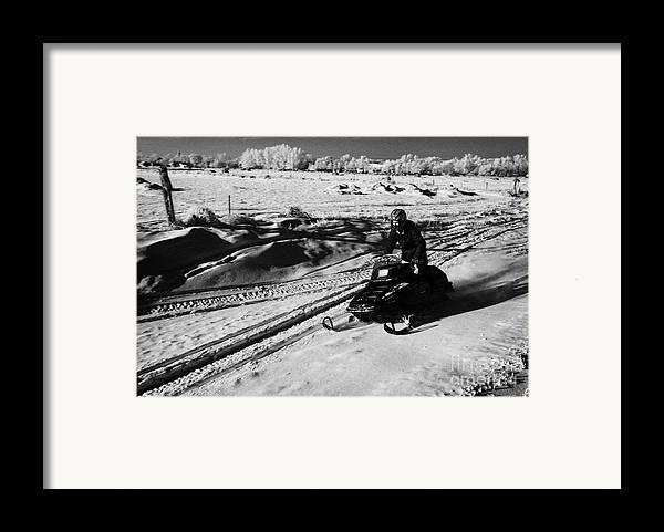 Man Framed Print featuring the photograph man on snowmobile crossing frozen fields in rural Forget Saskatchewan Canada by Joe Fox