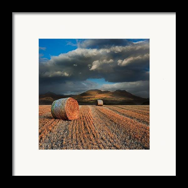 Landscape Framed Print featuring the photograph Landscape Of Hay Bales In Front Of Mountain Range With Dramatic by Matthew Gibson