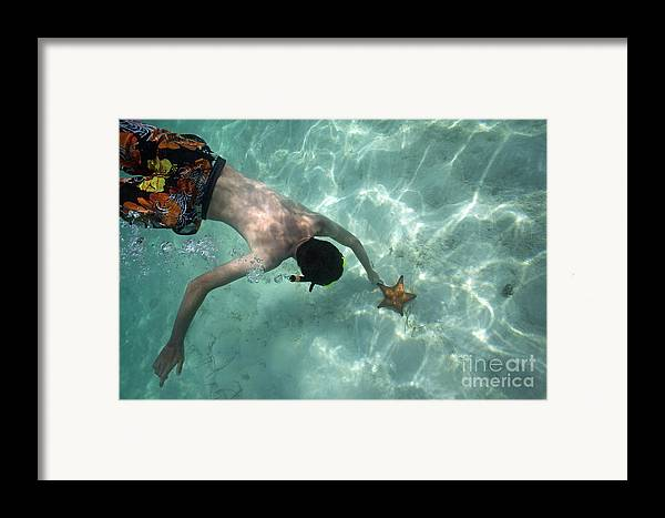 People Framed Print featuring the photograph Snorkeller Touching Starfish On Seabed by Sami Sarkis