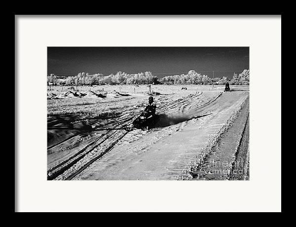 Man Framed Print featuring the photograph two men on snowmobiles crossing frozen fields in rural Forget Saskatchewan Canada by Joe Fox