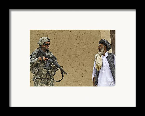 Afghan National Army Framed Print featuring the photograph U.s. Army Specialist Talks To An Afghan by Stocktrek Images