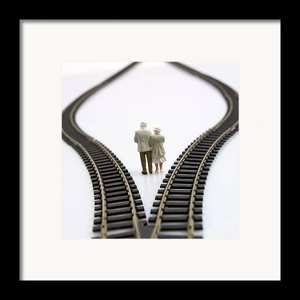 Contemplates Framed Print featuring the photograph Figurines Between Two Tracks Leading Into Different Directions Symbolic Image For Making Decisions. by Bernard Jaubert
