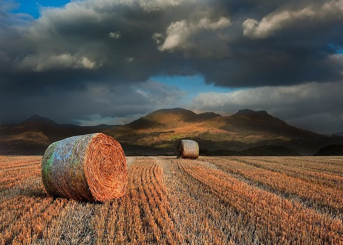 Landscape Greeting Card featuring the photograph Landscape Of Hay Bales In Front Of Mountain Range With Dramatic by Matthew Gibson
