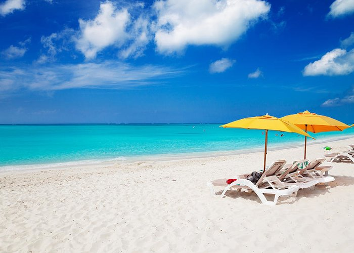 Grace Bay Greeting Card featuring the photograph Lounge Chairs And Yellow Umbrellas by Jo Ann Snover
