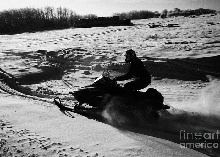 Man Greeting Card featuring the photograph man on snowmobile crossing frozen fields in rural Forget Saskatchewan by Joe Fox
