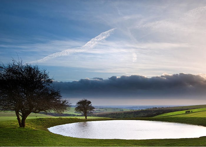 Landscape Greeting Card featuring the photograph Naturally Formed Dew Pond In Countryside Landscape With Moody Sk by Matthew Gibson