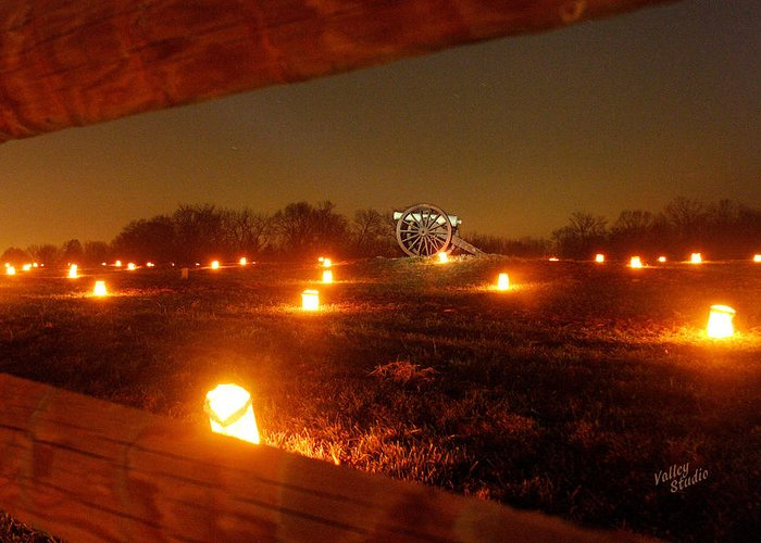 Looking Through A Split-rail Fence At A Solitary Cannon That Sits In The Middle Of This Field And Is Surrounded By Hundreds Of Luminaries. Each Year 23 Greeting Card featuring the photograph Solitary Cannon 12 by Judi Quelland