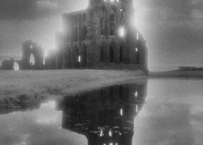 Eerie; Atmospheric; Spooky; Haunted; Haunting; Dramatic; Striking; Misty; Hazy; Lake; Reflection; English; Architecture; Exterior; Ruin; Ruins Greeting Card featuring the photograph Whitby Abbey by Simon Marsden