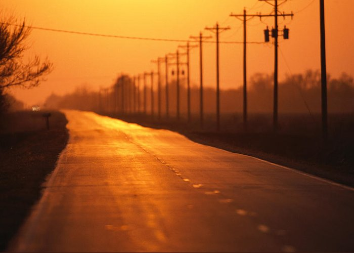 Roads Greeting Card featuring the photograph A Country Highway Fades Into The Sunset by Joel Sartore